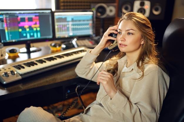 Dj femminile in registrazione di ascolto in cuffia, studio di registrazione interno sullo sfondo. sintetizzatore e mixer audio, posto di lavoro del musicista, processo creativo