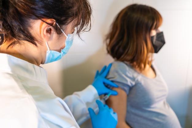 Dottoressa che applica il vaccino contro il coronavirus a una donna incinta. anticorpi, immunizza la popolazione.