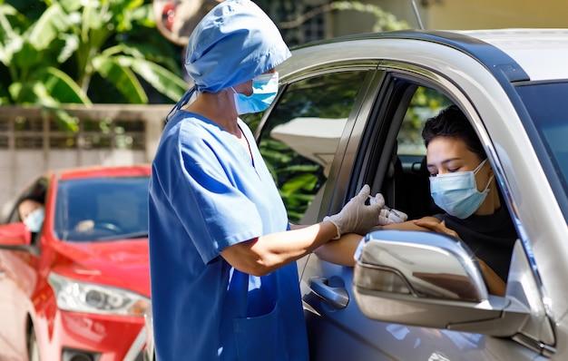 La dottoressa in uniforme ospedaliera blu e maschera facciale si trova vicino all'auto tenendo la siringa in mano indossa guanti di gomma che iniettano il vaccino covid 19 per guidare attraverso la spalla del paziente sulla coda di vaccinazione.