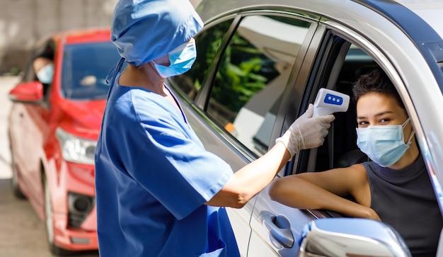 La dottoressa in uniforme ospedaliera blu e la maschera facciale stanno vicino alla guida attraverso la coda dell'auto tenere l'attrezzatura del termometro a infrarossi misurare la temperatura dalla fronte della paziente prima della vaccinazione.