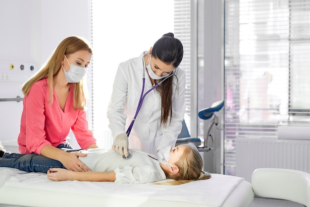 La dottoressa controlla il battito cardiaco e i polmoni usando lo stetoscopio durante l'epidemia di coronavirus, la madre sostiene la figlia del paziente, in maschere mediche