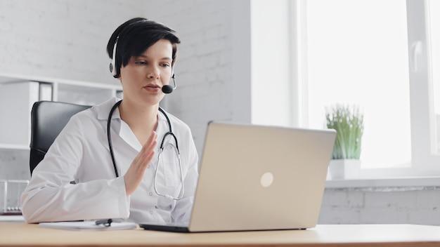 Medico femminile che consulta il paziente remoto online utilizzando la webcam sul computer portatile