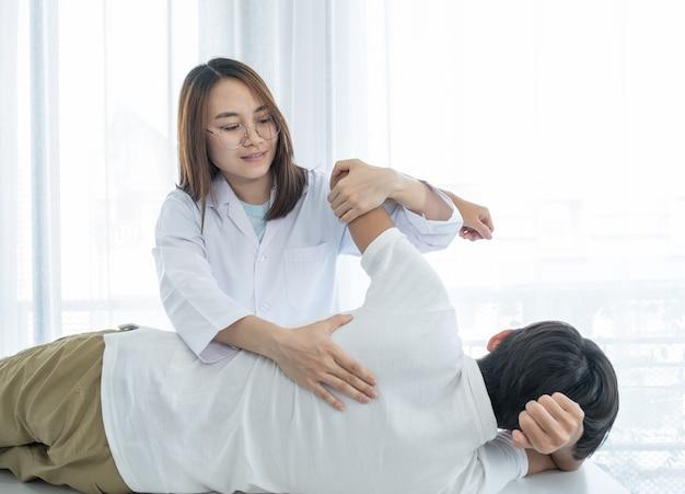 Dottoressa che fa terapia fisica estendendo la schiena di un paziente di sesso maschile.