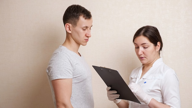 La dottoressa esamina la testa di un uomo calvo e compila una scheda di storia.