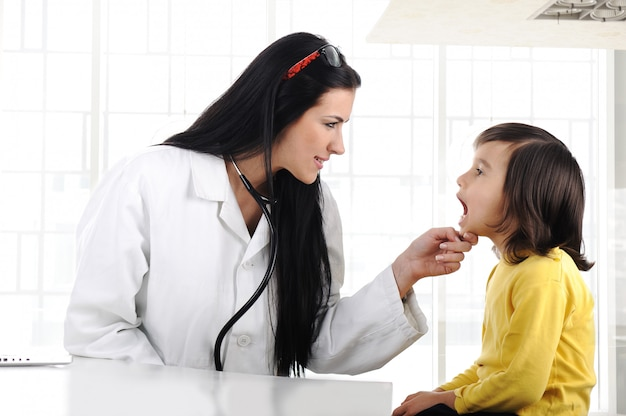 Bambino d'esame del medico femminile con l'abbassalingua