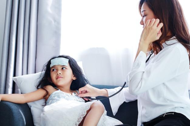 Medico femminile che esamina bambina con lo stetoscopio usato in un ospedale