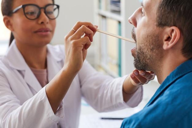 Medico femminile che esamina la gola del paziente durante la sua visita all'ospedale
