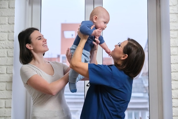 Medico femminile che esamina bambino del bambino. il pediatra ha preso in braccio il bambino, parlando con sua madre e ridendo insieme. pediatria, cura e salute dei bambini fino a un anno