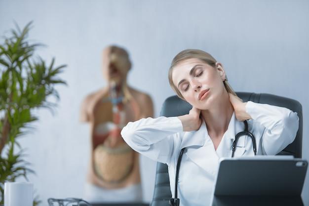 Una dottoressa si fa un massaggio al collo mentre è seduta alla sua scrivania