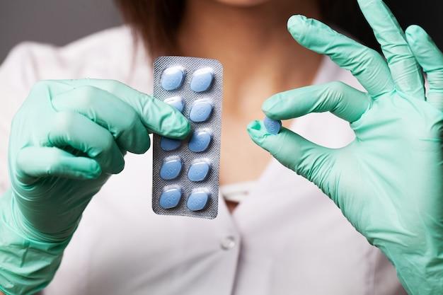 Dottoressa in guanti detiene pillole per la salute sessuale degli uomini