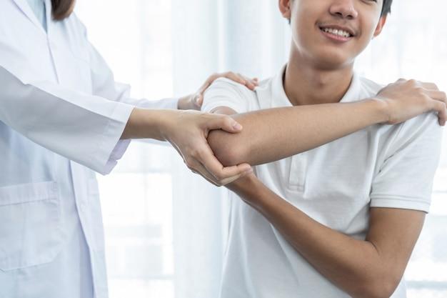 Mano femminile del medico che fa terapia fisica estendendo la spalla di un paziente maschio.