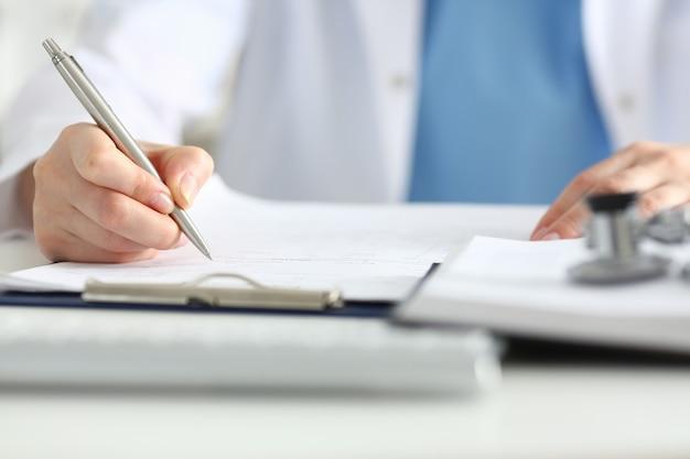 Medico femminile tenere in mano una penna d'argento che riempie l'elenco della storia del paziente