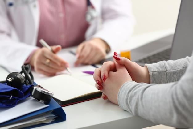 Mano femminile del medico che tiene la penna d'argento con il paziente