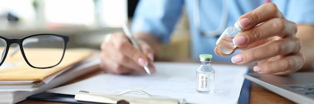 Mano di medico femminile che tiene la fiala di vaccino e facendo un primo piano di scartoffie