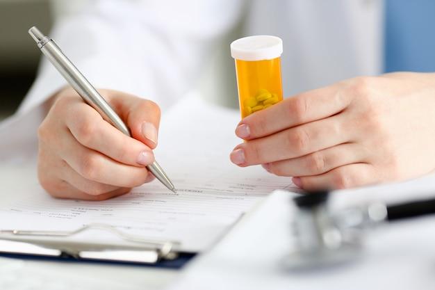 La mano femminile del medico tiene il barattolo delle pillole e scrive la prescrizione sul tavolo da lavoro.
