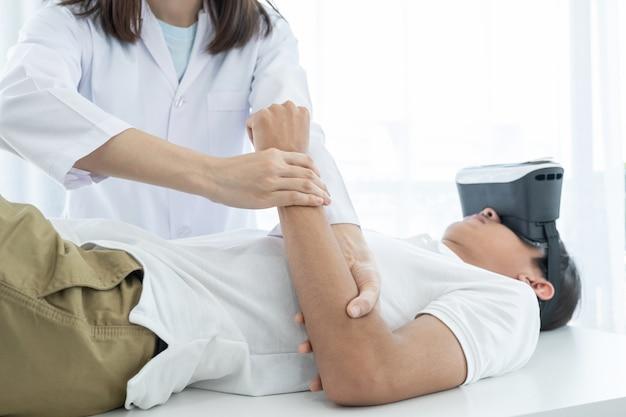 Mani di medico femminile che fanno terapia fisica estendendo il braccio di un paziente maschio con scatola vr