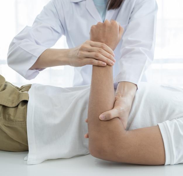 Mani femminili del medico che fanno terapia fisica estendendo il braccio di un paziente di sesso maschile.