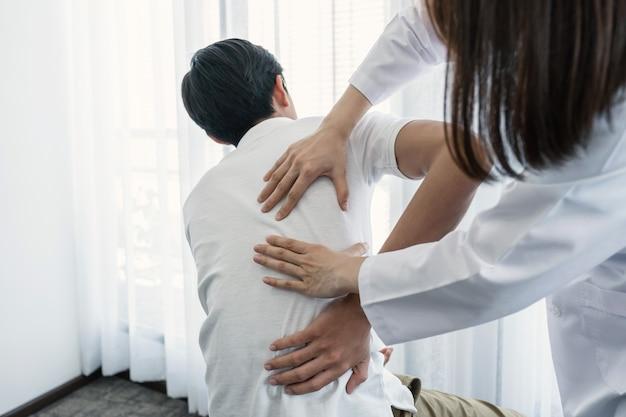 Mani femminili del medico che fanno terapia fisica estendendo la parte posteriore di un paziente maschio.