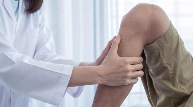 Mani femminili del medico che fanno terapia fisica estendendo la gamba e il ginocchio di un paziente di sesso maschile.
