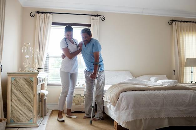 Medico femminile che aiuta uomo senior a camminare con le stampelle in camera da letto