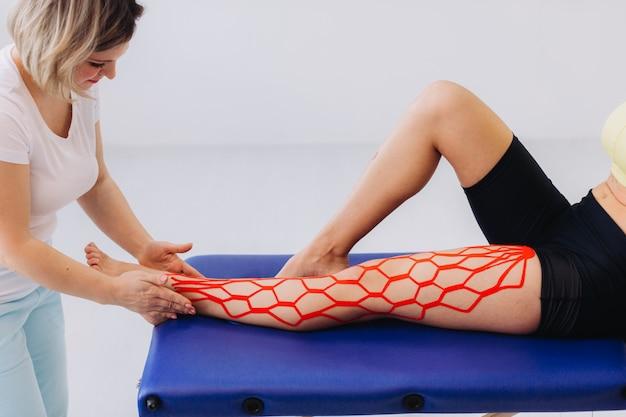 La dottoressa aiuta la donna mettendo il nastro kinesio sulla sua gamba. giovane donna caucasica con nastro terapeutico elastico kinesiologico sulla sua gamba