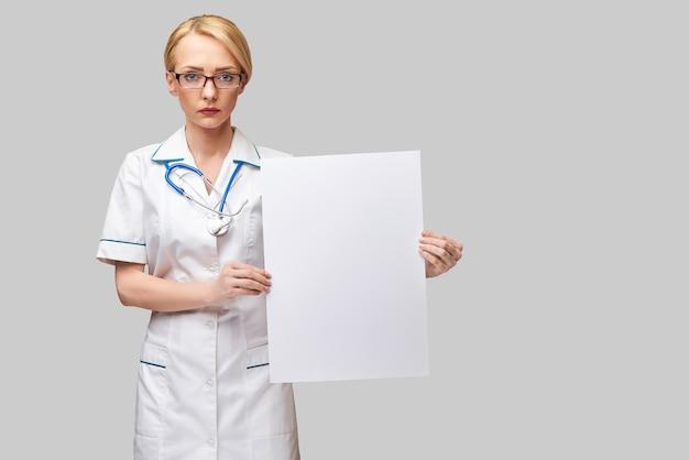 Medico femminile che tiene un foglio di carta bianco o un poster