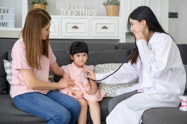 Uno stetoscopio della holding del medico femminile sta esaminando una ragazza felice in ospedale con sua madre, concetto medico