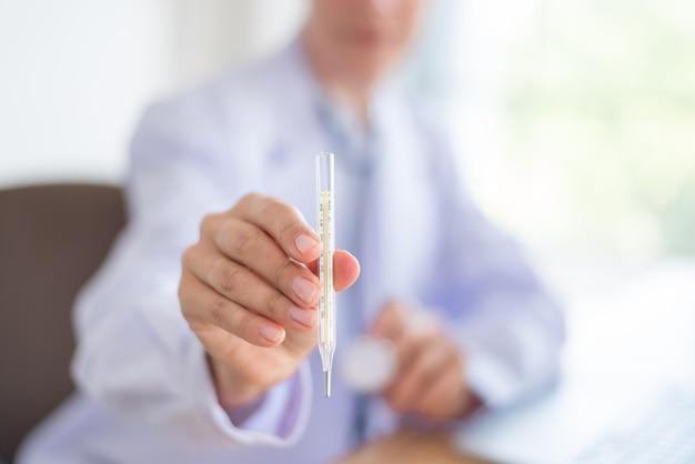Medico femminile che giudica un termometro pronto a controllo sanitario nella stanza dell'esame.