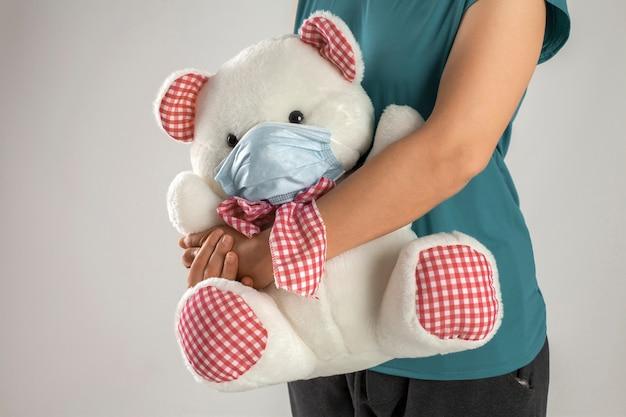 Il medico femminile abbraccia l'orsacchiotto bianco con gli accessori dei quadrati rossi e la maschera chirurgica