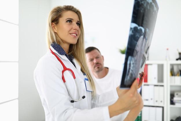 Il medico femminile sta tenendo una radiografia accanto al paziente seduto