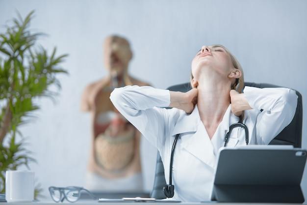 Una dottoressa massaggia un collo stanco mentre è seduta alla sua scrivania