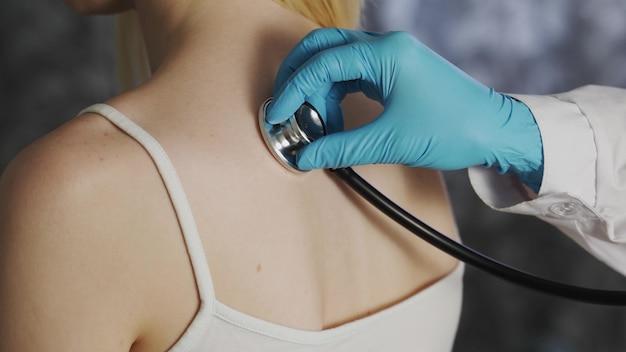 Medico femminile che ascolta la parte posteriore del suo paziente con uno stetoscopio. dottoressa usando il suo stetoscopio per ascoltare il polmone della sua paziente mentre respira.