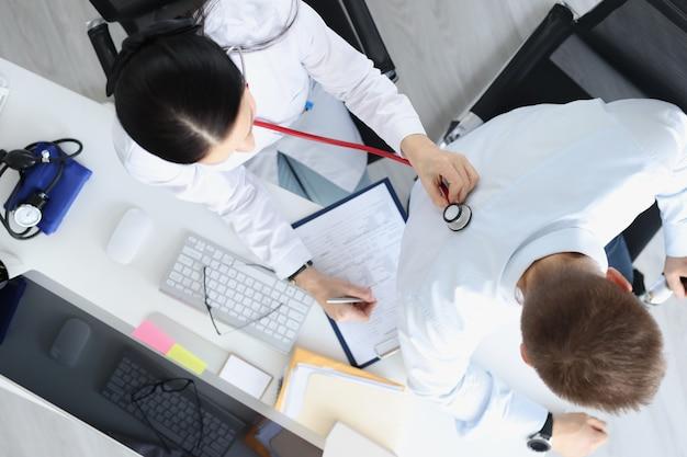 La dottoressa ascolta i polmoni del paziente maschio alla reception vista dall'alto diagnosi di malattia polmonare