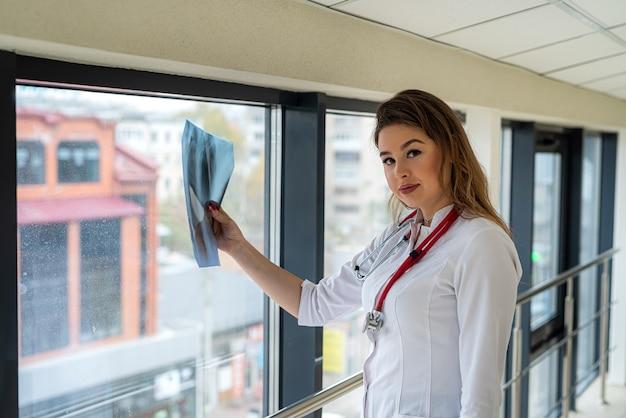 Medico femminile che esamina immagine a raggi x della radiografia dei polmoni in clinica
