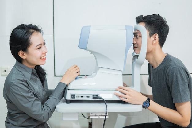 Una dottoressa e un paziente maschio che fanno un controllo della vista utilizzando un dispositivo in una clinica oculistica