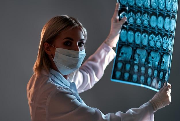 Medico femminile in una maschera esamina una scansione a raggi x o mri di una scansione del cervello di pazienti isolata sul nero.