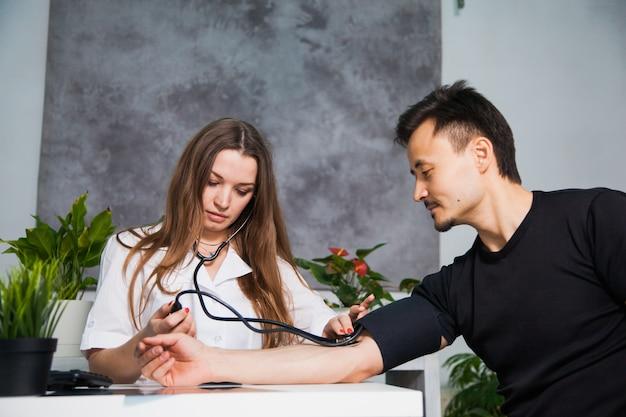 Medico femminile che misura la pressione sanguigna arteriosa per il paziente sul tonometro alla clinica. concetto di assistenza sanitaria e medico