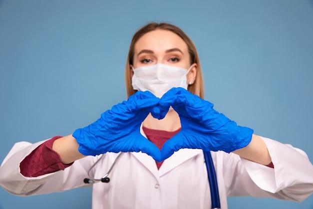 La dottoressa in un camice medico mostra un cuore con le sue mani