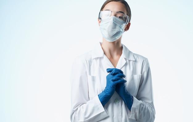 Medico femminile in un abito medico e test di vaccinazione guanti blu