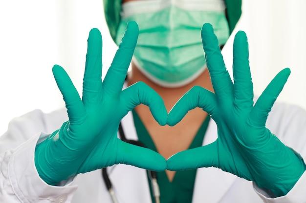 La maschera medica del medico femminile e le mani nel guanto di lattice mostrano il simbolo del cuore