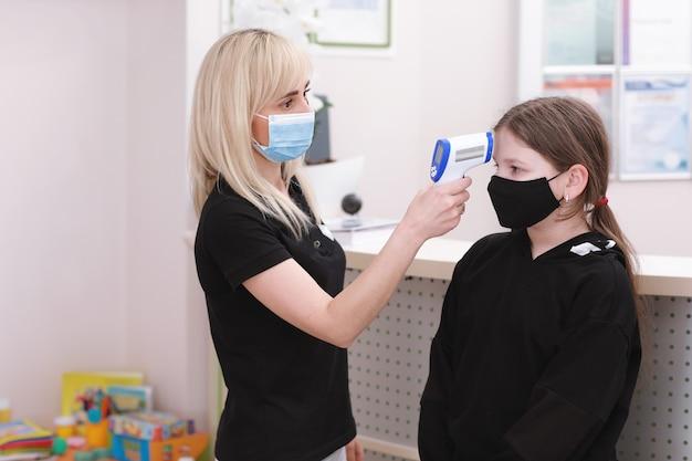 Medico femminile nella mascherina medica con la febbre di misurazione della pistola del temometro a infrarossi senza contatto