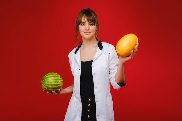Un'infermiera medico femminile in camice bianco con frutta in mano si pone su un rosso