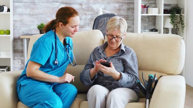 Dottoressa in casa di cura seduta sul divano che insegna a una donna anziana a usare lo smartphone