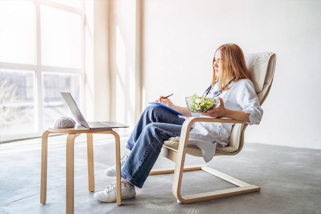 Il nutrizionista medico femminile conduce la consultazione online con il computer portatile.