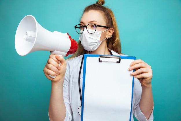 Medico femminile in tuta protettiva e occhiali con maschera tiene il megafono e tablet