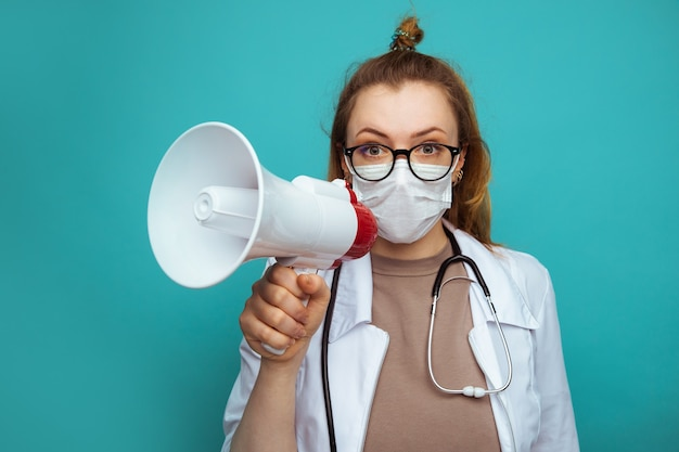 Medico femminile in tuta protettiva e occhiali con maschera tiene il megafono.