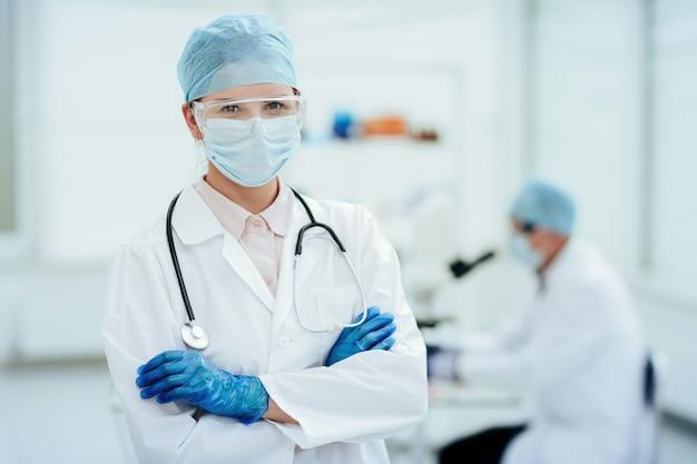 Dottoressa in indumenti protettivi in piedi in laboratorio.