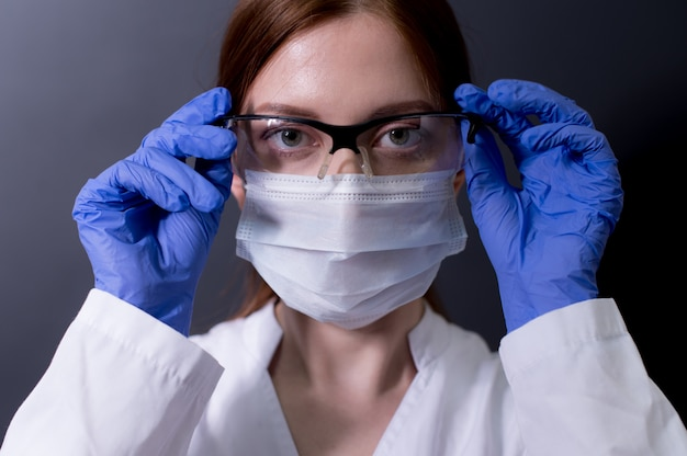 Dottoressa in tuta protettiva, maschera medica e occhiali
