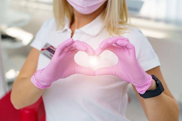 Le mani del medico femminile che mostrano la forma del cuore. primo piano delle mani del medico. aiuto medico, profilassi o concetto di assicurazione. assistenza cardiologica, salute, protezione e prevenzione. concetto di cuore sano