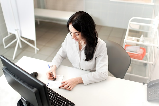Medico femminile che lavora al computer portatile, scrivendo il blocco note di prescrizione con informazioni record sullo scrittorio in ospedale o clinica, sanità e concetto medico
